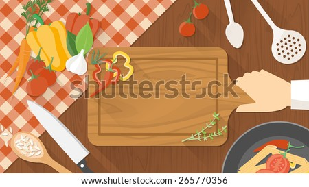 Kitchen wooden worktop with cook's hand holding a chopping board, kitchen tools and vegetables all around, top view