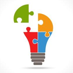 light bulb with four puzzle parts symbolizing teamwork ideas