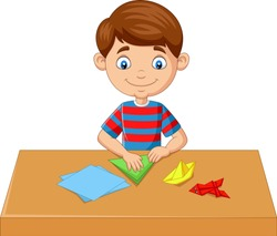 Little boy folding paper and making origami toys