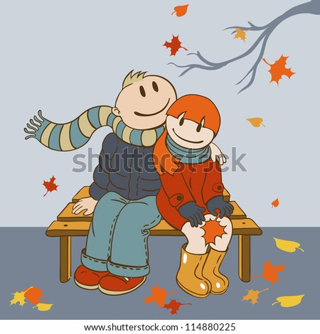 Loving couple sitting on a bench and admire the falling leaves