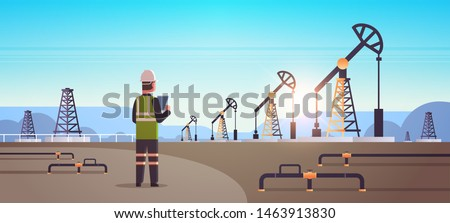 male engineer refinery worker using tablet oil pump rig energy industrial zone oil drilling fossil fuels production concept flat mountains sunset background horizontal full length