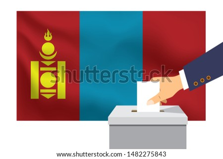 Male hand puts down a white sheet of paper with a mark as a symbol of a ballot paper against the background of the Mongolia flag. Mongolia the symbol of elections.