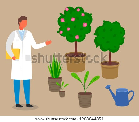Male scientist, botanist studies and analyzes the plant. Cultivation and processing of plant. Laboratory worker man in a scientist uniform studying different vegetation rules for care and watering ストックフォト ©