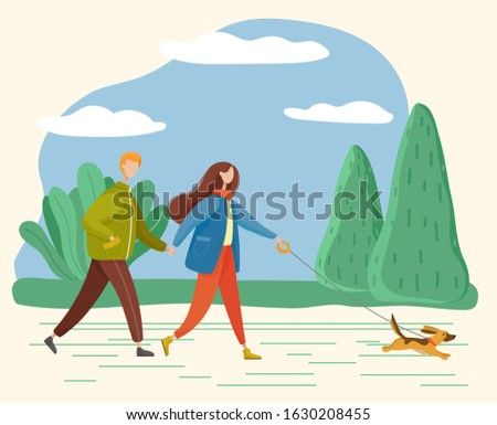 man and woman strolling in park