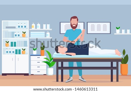 man patient lying on massage table therapist doing healing treatment massaging injured hand manual physical therapy rehabilitation concept full length modern hospital office interior horizontal