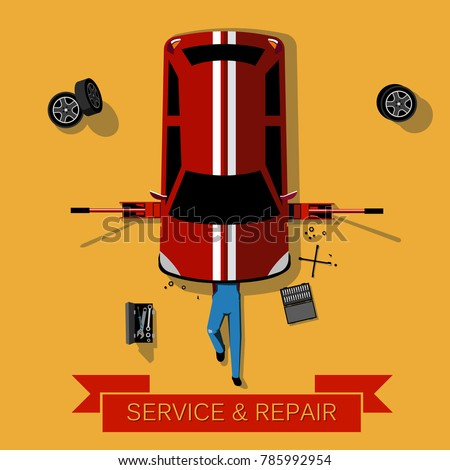 Mechanic lies under the car and repairs it: Car repair and service concept: Top view