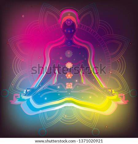 Meditating human in lotus pose in universe beside the stars. Yoga, esoterics; seven chakras and aura glow. Mandala background.