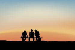 men sitting and talking at sunset