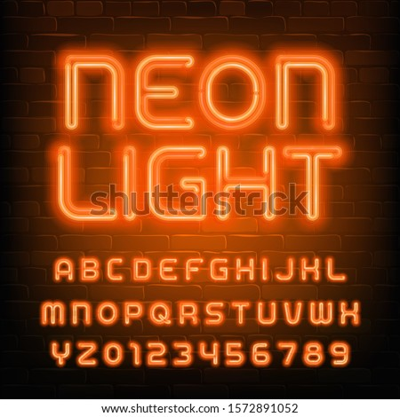 Neon Light alphabet font. Simple orange neon letters and numbers. Brick wall background. Stock vector typescript for your typography design.