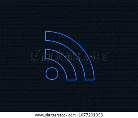 Neon light. RSS sign icon. RSS feed symbol. Glowing graphic design. Brick wall. Vector