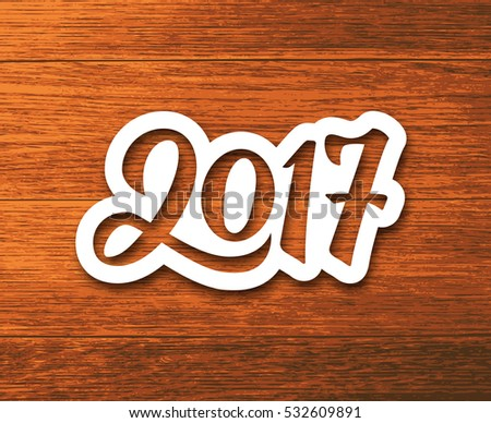 New Year 2017 paper label with calligraphic number on wood background. Vector greeting card design template for winter holidays