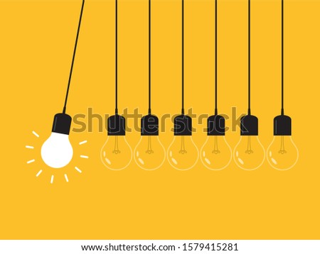 Newton's cradle with glowing light bulb. Pendulum. Leadership, power and uniqueness concept.