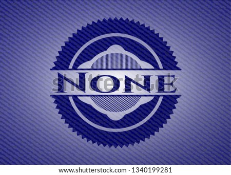 none badge with denim background