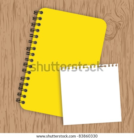 Notebook with paper on wood background