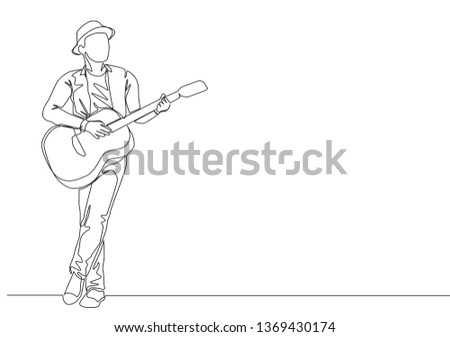 One continuous line drawing of young happy male guitarist wearing hat and playing acoustic guitar on street road. Musician artist performance concept single line draw design illustration