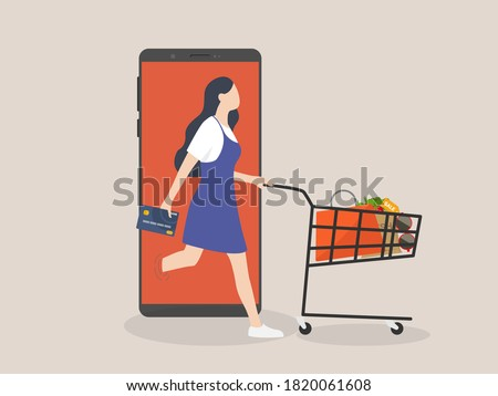 Online shopping or mobile shopping app concept, woman consumer holding credit cart pushing full of goods and box packages in shopping cart trolley running from website or app on mobile smart phone
