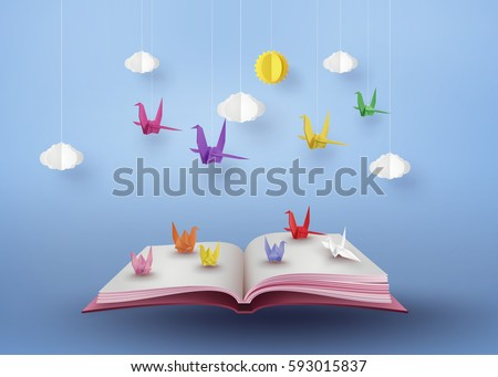 origami made colorful paper bird flying over open book and  blue sky with cloud . paper art and  digital craft style.  stock photo