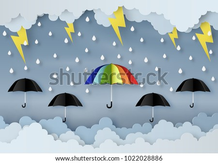 Origami made rainy weather forecast of Water drop on the colorful and black umbrella with thunder in the sky, paper art design and craft style.