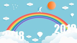 Paper art style vector illustration graphic design of young man walking on the rainbow from year 2018 to year 2019 over the sky.
