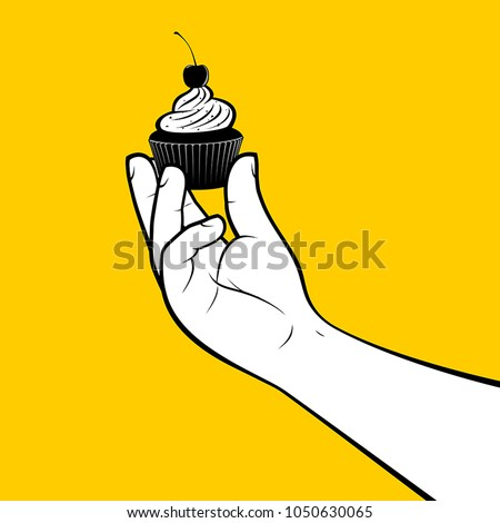 pastry cook holding cupcake