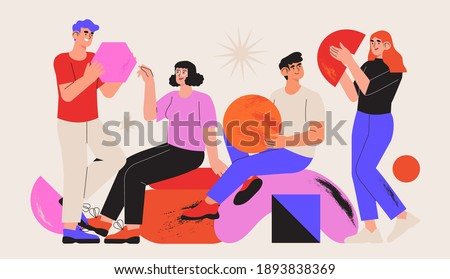 People organize abstract geometric shapes scattered around them. Young men and women collecting figures and organise them. Concept of teamwork. Team or colleagues work together on creative project.