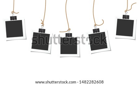 Polaroid square frames hanging on a black paper clip and beautiful shadow on white background.