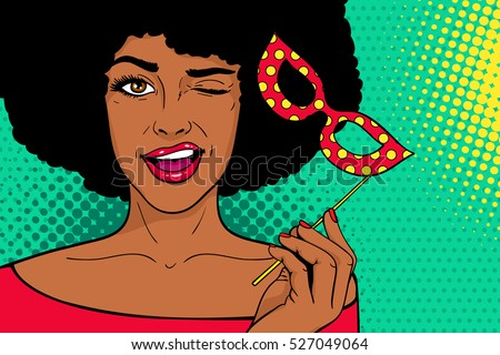 Pop art female face. Young sexy african woman with carnival mask in her hand smiling and winking on dots background. Vector illustration in retro comic style. Holiday party invitation poster.