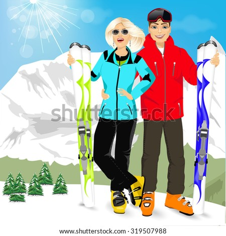 portrait of happy couple skiers standing on edge of mountain peaks on background of snowy mountains in ski resort