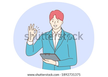Positive emotions, ok sign and gesture language concept. Young positive businessman cartoon character standing with tablet or documents in hand and showing agree okay success sign with fingers  ストックフォト ©