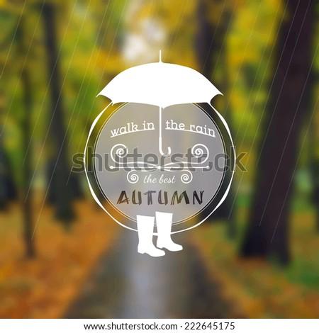 Poster with autumn landscape. Motto, slogan for autumn season. Umbrella and rubber boots on a autumn park background. Walk under the autumn rain. Circle emblem of  autumn season on a photo background.
