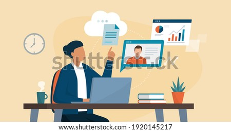 Professional business woman sitting at desk and connecting with her laptop, she is video calling her colleague and sharing files online on the cloud