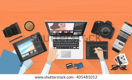 Professional photographer working at office desk, he is editing his pictures using a laptop and a graphic tablet