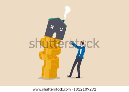 Property and housing market collapse, real estate stock risk or economic recession concept, businessman house owner or real estate agent help protect the house to fall off unstable stack of coins. ストックフォト ©
