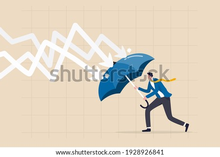Protection or defensive stock in economy crisis or market crash, business resilient to survive difficulty or insurance concept, businessman holding umbrella to cover and protect from downturn arrow.
