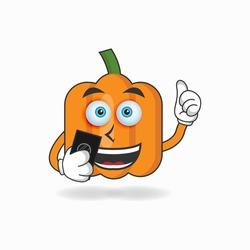 Pumpkin mascot character holding a cellphone. vector illustration