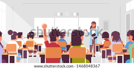 pupils group listening to female teacher schoolboy raising hand to answer in classroom during lesson teaching education concept modern class room interior flat horizontal portrait