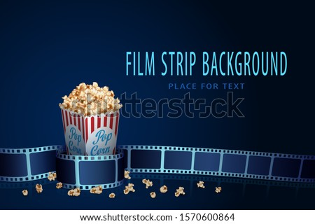 Real film strip frame in wave form with popcorn box isolated on blue background. Cinema template with space for your text. 3D design flyer or poster festival. Movie time and cinematography concept.