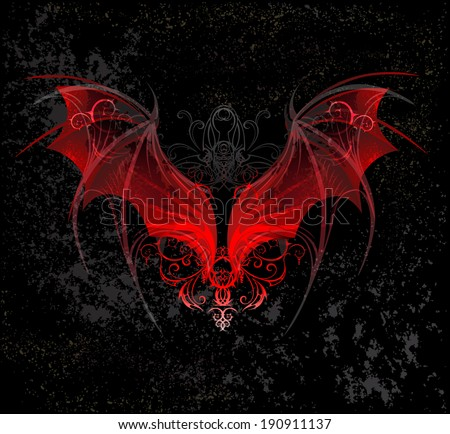 Red dragon wings decorated with pattern on black textural background.