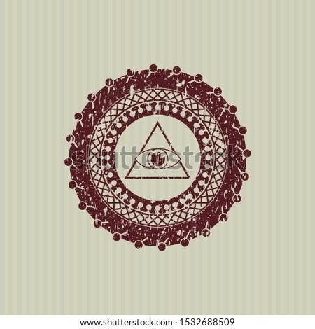 Red illuminati pyramid icon inside distress rubber seal