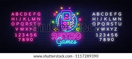 Retro Games Vector Logo. Retro geek gaming gamepad in hand neon sign, modern trend design, vivid vector illustration, promotional character games. Vector Illustration. Editing text neon sign
