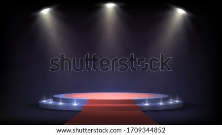 Round stage with steps and spotlights, red carpet on a pedestal