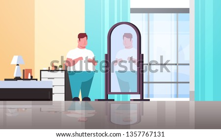 sad overweight man looking at himself reflection in mirror guy over size obesity concept modern apartment bedroom interior flat full length horizontal