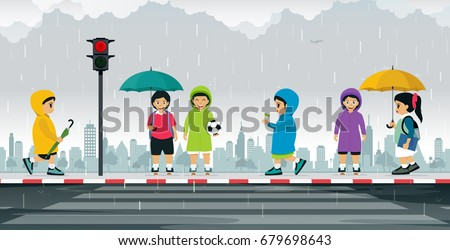 Schoolboy wears a raincoat and holds an umbrella to protect the rain.