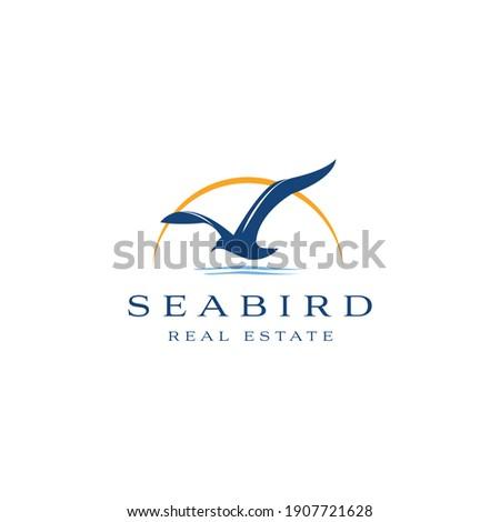 Seabird real estate logo design. Seagull luxury property template vector symbol. Sea Bird fly silhouette sign Stockfoto ©