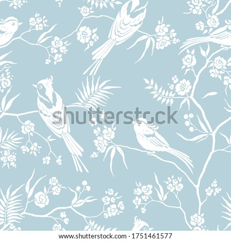 Seamless pattern in oriental style with blooming branches trees and birds. Wildlife silhouette, white floral ornament on blue background. Vector hand drawn illustration, garden in japanese style.