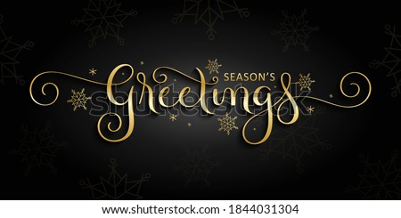 SEASON'S GREETINGS metallic vector gold brush calligraphy banner with spiral swashes on black background stock photo