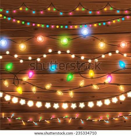Stock Photo Set of Glowing Christmas Lights for Xmas Holiday Greeting Cards Design. Wooden Hand Drawn Background. Light Bulbs Collection.
