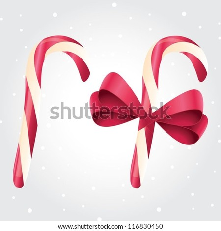 Set of 2 isolated red and white candy canes. One with red satin ribbon.