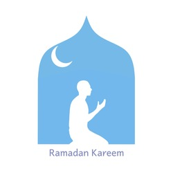 Silhouette of a man praying inside a blue mosque. Good for your banner, poster, background, card, etc.
