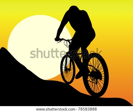 silhouette of a mountain  biker  in the sun and the orange sky